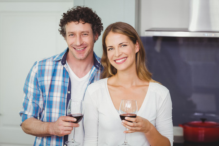 causal clothing: Portrait of smiling young couple holding wineglasses in kitchen at home