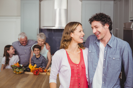 causal clothing: Happy family laughing in kitchen at home