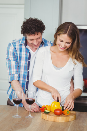 causal clothing: Smiling wife with husband standing in kitchen at home
