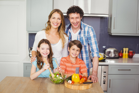 causal clothing: Portrait of smiling family preparing vegetable salad in kitchen