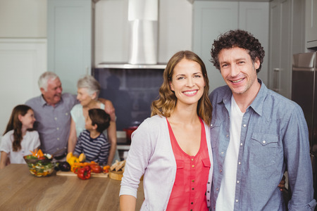 causal clothing: Portrait of smiling couple standing with family in kitchen at home Stock Photo