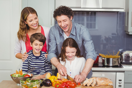 causal clothing: Father cutting vegetable with wife and children in kitchen at home Stock Photo