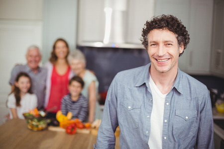 causal clothing: Portrait of smiling young man standing with family in kitchen