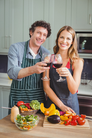 toasting wine: Portrait of happy couple toasting wine in kitchen at home