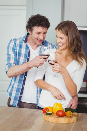 toasting wine: Young couple toasting wine while standing in kitchen at home Stock Photo