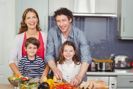 causal clothing: Portrait of smiling parents with children in kitchen at home