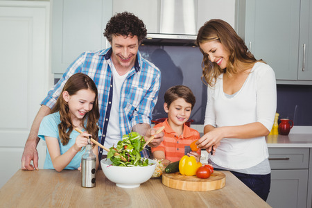 causal clothing: Happy family preparing vegetable salad in kitchen
