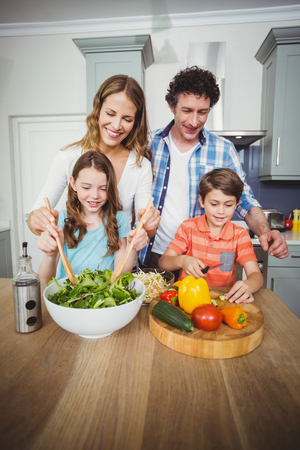 causal clothing: Young happy couple standing with children in kitchen at home