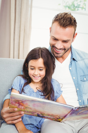 Smiling father with daughter reading book while sitting on sofa at home