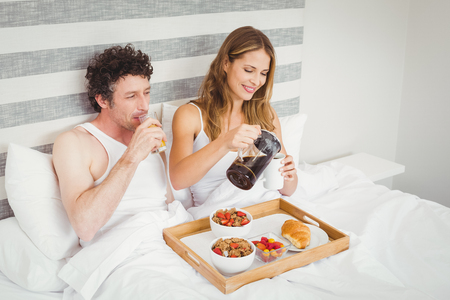 causal clothing: Smiling couple having breakfast while resting on bed at home