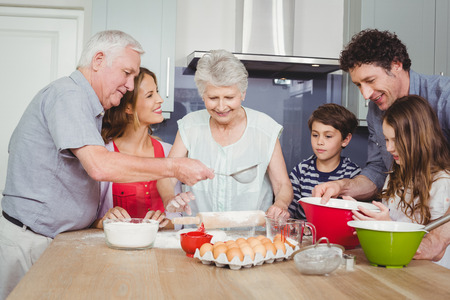 causal clothing: Smiling family preparing food in kitchen at home Stock Photo