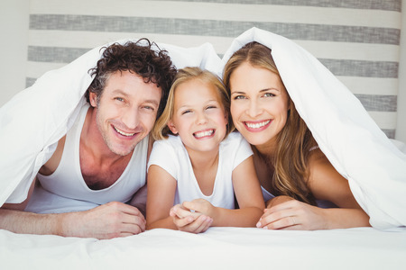 duvet: Portrait of happy family covered with duvet on bed at home
