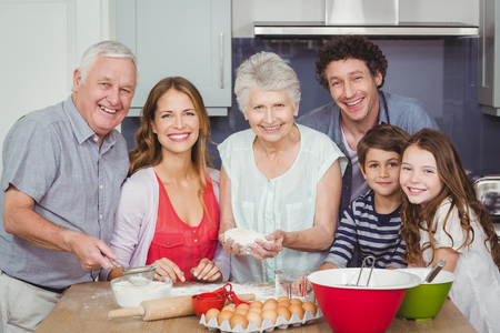 causal clothing: Portrait of smiling happy family cooking food in kitchen at home Stock Photo