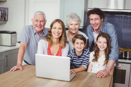 causal clothing: Portrait of happy family using laptop on table in kitchen at home
