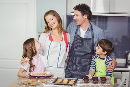 causal clothing: Smiling happy family standing in kitchen at home
