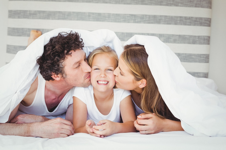 duvet: Parents kissing daughter covered with duvet on bed at home Stock Photo