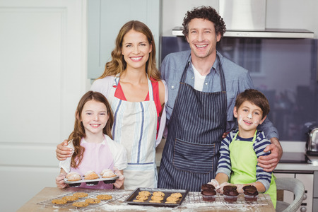 causal clothing: Portrait of smiling happy family standing in kitchen at home