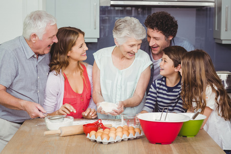 causal clothing: Smiling grandmother cooking food with family in kitchen at home Stock Photo