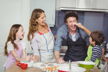 causal clothing: Happy family enjoying while cooking food in kitchen at home Stock Photo