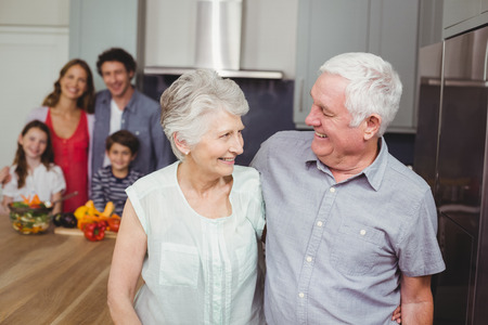 causal clothing: Happy grandparents standing with family in kitchen at home