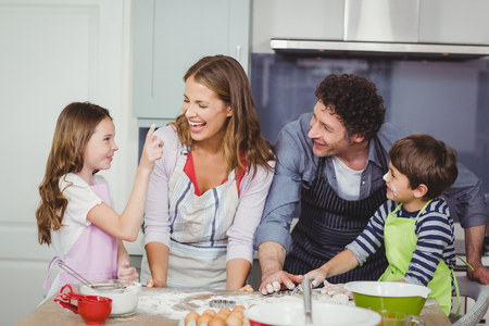 causal clothing: Family enjoying while cooking food in kitchen at home Stock Photo