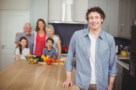 causal clothing: Portrait of happy young man standing with family in kitchen at home Stock Photo