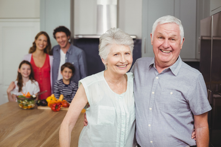 causal clothing: Portrait of smiling grandparents standing with family in kitchen at home Stock Photo