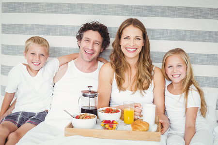 causal clothing: Portrait of smiling happy family having breakfast on bed at home Stock Photo