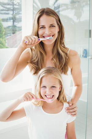 routine: Portrait of smiling mother and daughter brushing teeth at home