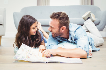 picture book: Happy father and daughetr with picture book lying on floor at home Stock Photo