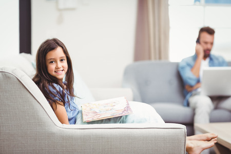 picture book: Portrait of happy girl with picture book sitting on sofa while father in background