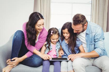 Familia que mira en la computadora de la tableta mientras está sentado en el sofá en casa