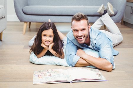 picture book: Portrait of father and daughter with picture book lying on floor at home