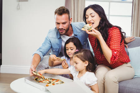 eating fast food: Family of four eating pizza while sitting on sofa at home