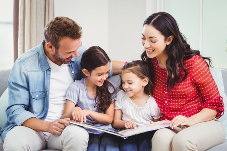 picture book: Happy parents looking in picture book while sitting with daughters on sofa at home