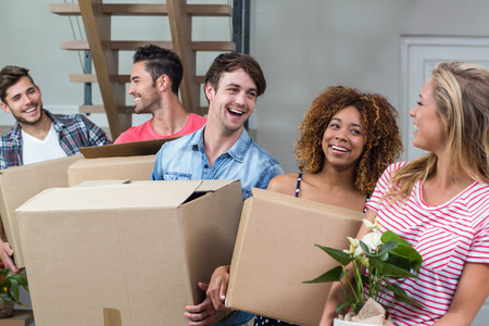 relocating: Happy young friends carrying boxes while relocating in new house Stock Photo