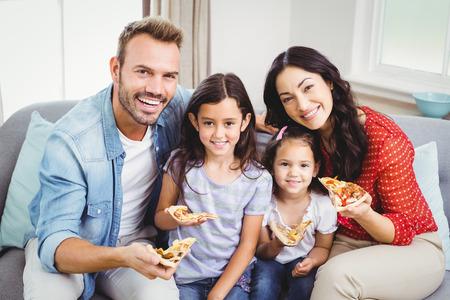 familia comiendo: Retrato de familia feliz comiendo pizza mientras está sentado en el sofá en casa Foto de archivo