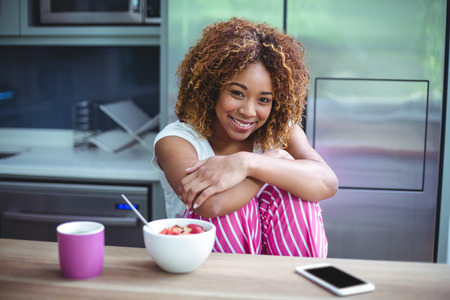 hugging knees: Portrait of happy woman sitting by table during breakfast