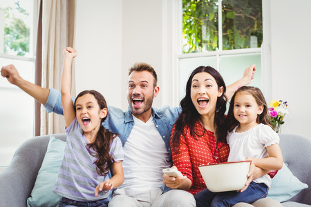 Happy family cheering while watching TV at home