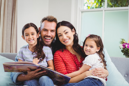 picture book: Portrait of happy family with picture book sitting on sofa at home