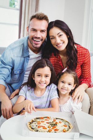 Happy family of four enjoying pizza at home photo