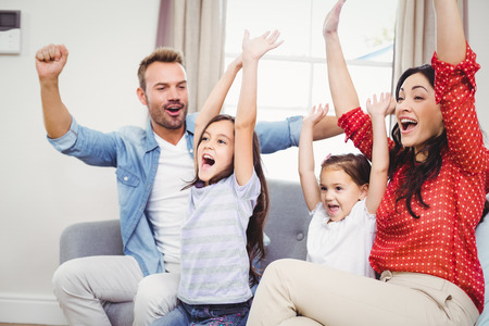 Family cheering while sitting on sofa at home photo