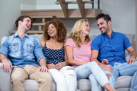Cheerful young friends sitting on sofa at home