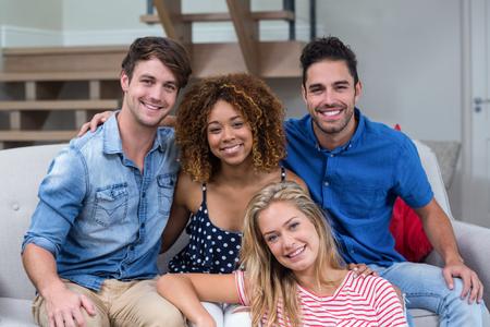 trato amable: Retrato de j�venes amigos felices sentado en el sof� en casa