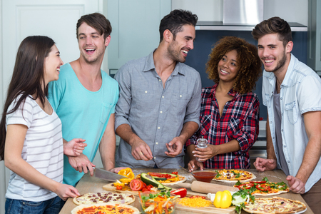 multiethnic: Cheerful multi-ethnic friends preparing pizza on kitchen table at home