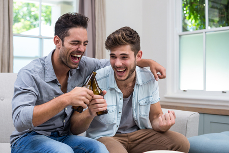 trato amable: amigos varones alegre tostado cerveza mientras est� sentado en el sof� en casa Foto de archivo
