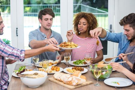 tomando refresco: j�venes amigos multi�tnicas que tienen la comida a la mesa en casa