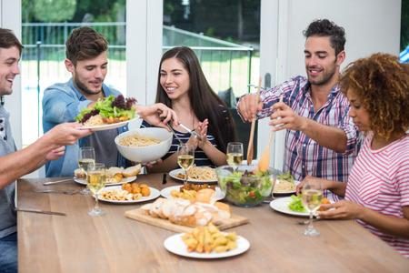 tomando refresco: Amigos felices multi-étnicos que tienen la comida a la mesa en casa