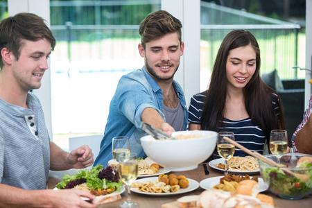 tomando refresco: jóvenes amigos que la comida a la mesa en casa