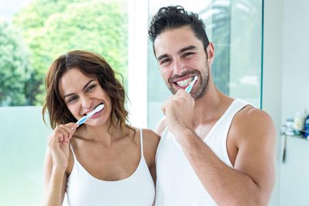 Portrait of happy young couple brushing teeth in bathroom
